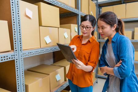 아름 다운 예쁜 여성 직원 창 고에서 작업하는 모바일 패드 컴퓨터를 사용 하 고 온라인 쇼핑 주문 문서를 재고 상품을 확인합니다. 스톡 콘텐츠