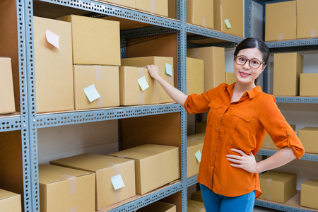 happy professional online shopping store manager woman standing in warehouse looking at camera smiling when she checking company stock goods. Reklamní fotografie