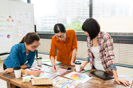 professional young female designer meeting in office with employees and pointing color document explaining how to design new case.