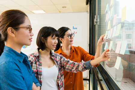 young pretty office worker women looking at glass window wall meeting and using sticky post note paper plan new work design.