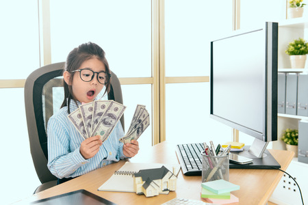 young cute female kid children house agent earning many money and sitting in office counting personal banknote feeling surprised. Stock Photo