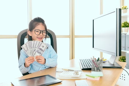happy pretty kid girl office worker showing company marketing banknote money looking at camera smiling when she sitting in office.