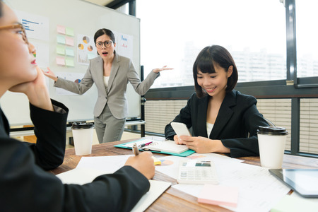 pretty young company female business manager looking at employees feeling angry when she finding they don't joining  meeting report. Foto de archivo