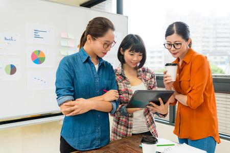 équipe de designers attrayante et professionnelle utilisant un ordinateur de bureau mobile et visualisant des informations en ligne pour rechercher une nouvelle inspiration. Banque d'images