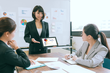 smiling beautiful business speaker using with mobile digital tablet computer presenting case planning to company partner during meeting.