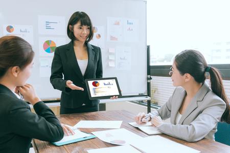 lachend mooie zakelijke spreker met behulp van mobiele digitale tablet-computer presenteren van case planning aan de bedrijfspartner tijdens de vergadering.