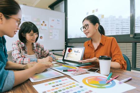 예쁜 여자 관리자 모바일 다이어그램 패드를 사용 하여 디자인을 보여주는 웃는 회사 모임 동안 그녀의 디자이너 동료에 대 한 계획. 스톡 콘텐츠