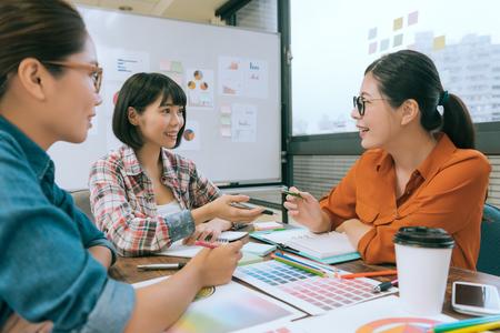 Professionelle hübsche Frauen Büroangestellte, die auf Konferenzschreibtisch sprechen und Treffen haben, um neue Entwurfsfallplanung zu besprechen.