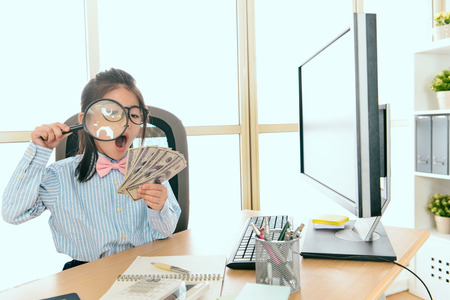 beauty young little female company manager holding many banknote money sitting in office and using magnifier looking feeling shocked. Stok Fotoğraf