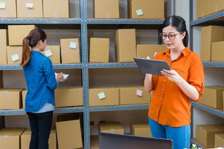 pretty elegant woman manager using mobile digital tablet working and her employee girl checking online shopping order parcel when they standing in warehouse together.