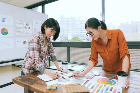 プロの美容女性デザイナー チーム会議机会議とカラフルな紙のドキュメントが選択色を議論することを指します。
