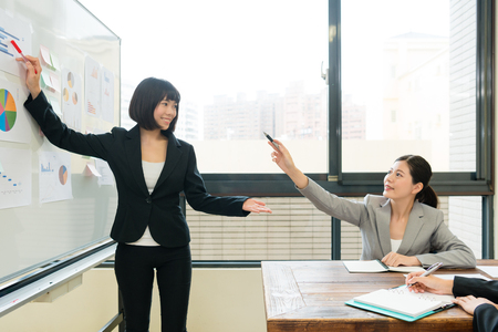 professional happy female company boss pointing whiteboard document asking problem when her employee making report during meeting. Stock Photo