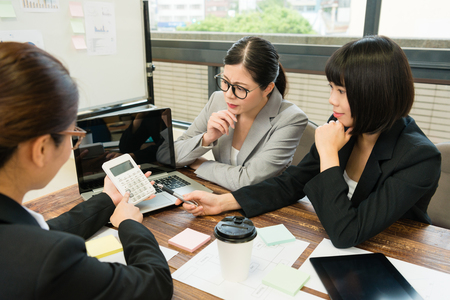 高角度新しいケースと同僚との議論のための会社の予算をカウントする計算機を使用してビジネス ワーカーの女性の写真を見る。