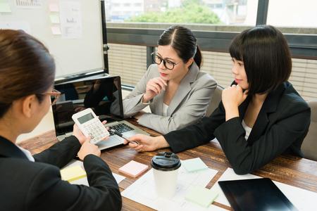 Photo grand angle de vue d'une femme travailleuse à l'aide d'une calculatrice comptant le budget de l'entreprise pour un nouveau cas et une discussion avec des collègues. Banque d'images - 89273963