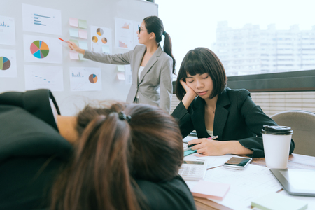 beautiful professional business manager woman using whiteboard showing document report but her colleague feeling boring and sleeping during meeting. selective focus photo.