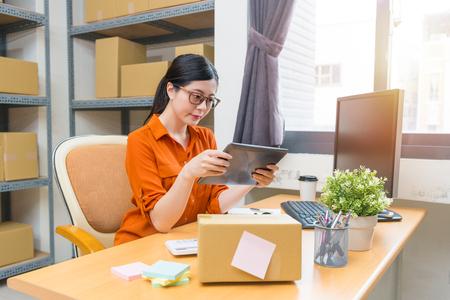 モバイルデジタルタブレットパッドを使用して美しいかわいい女性のオフィスワーカーは、オンラインショッピングの注文やブラウジングの販売状 写真素材