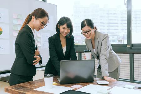 행복 한 예쁜 사무실 근로자 팀웍 회의 및 랩톱 컴퓨터를 찾고 사무실에서 서있는 사례 계획 아이디어를 찾고.