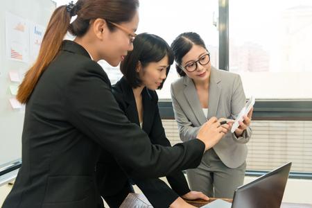 Hübscher junger weiblicher Geschäftsführer, der den Taschenrechner verwendet, der das Firmenbudget für Kollegen zählt und neuen Fallplan bespricht. Standard-Bild - 89274040