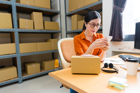 attractive beauty girl online shopping owner using mobile smart phone checking client order and sitting on warehouse working desk preparing shipping box.