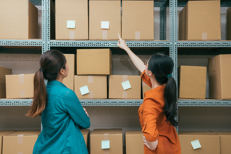 back view photo of online shopping company office workers looking at shipping box and pointing order memo confirm warehouse stock with vintage retro film color. Banco de Imagens