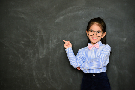 beautiful happy kid teacher standing in chalk blackboard background and face to camera showing class teaching writing area. Reklamní fotografie