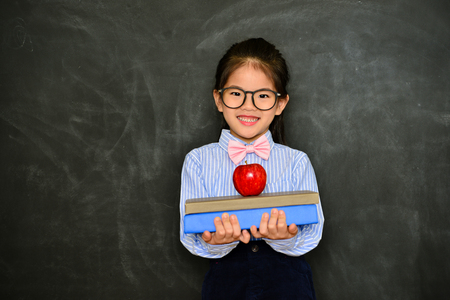 smiling young little girl children showing back to school concept with books and apple isolated on blackboard background. Stock Photo