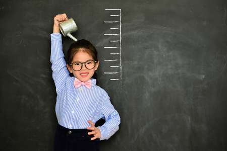 confidence happy girl kid face to camera smiling and irrigating body measured growth height isolated on black chalkboard background. Stok Fotoğraf