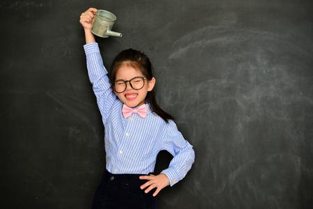beautiful pretty little girl using watering bottle irrigated body want to higher and feeling fear standing in blackboard background. 版權商用圖片