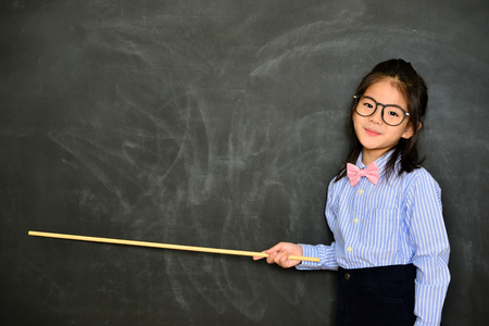 smiling pretty little teacher using stick pointing chalkboard empty screen showing school studying concept standing in blackboard background. Foto de archivo