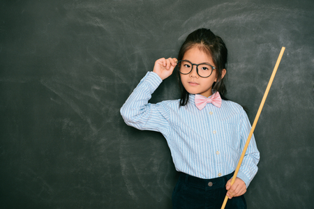 confident smart little girl dressed as teacher standing in black chalkboard background and holding stick looking at camera. school concept.