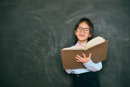 幸せな甘い少し英語教師学校の授業中に生徒を指導し、黒板背景に立って研究本を使用します。 写真素材 - 89274440