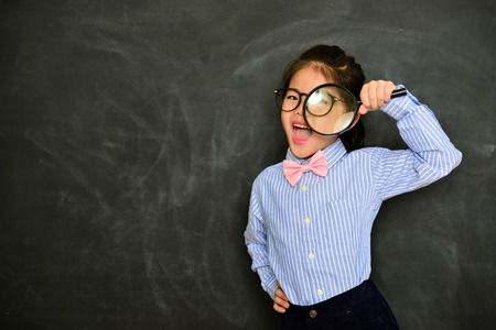happy cheerful female little teacher using magnifier researching school studying information and standing in front of chalkboard background looking at camera.