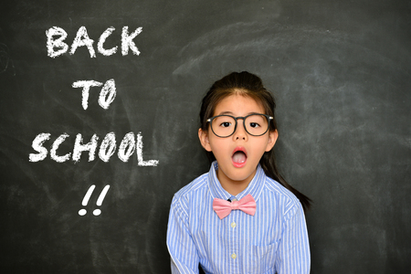 lovely pretty female little children face to camera showing shocked emotion when she must to back to school studying but her homework  unfinished isolated on blackboard background.