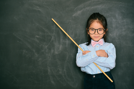 young attractive little female teacher holding stick standing in front of blackboard feeling angry when her student making mistake.