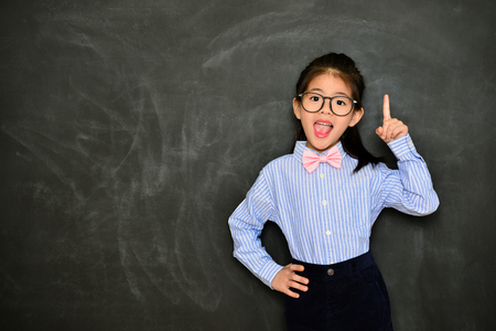 happy cheerful little girl teacher showing school education concept and standing in blackboard background having good idea.