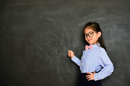 プロ笑みを浮かべて小さな女の子教授黒板と教育授業研究授業内容を書くチョークを使用して。