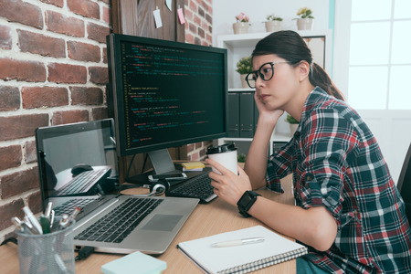 pretty beauty lady computer worker looking at code data feeling worried when she development new online security system having problem.