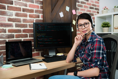 beautiful smiling female programmer worker wearing headset microphone sitting on workplace and looking at camera smiling. Stock Photo