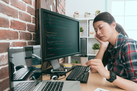 pretty elegant lady computer developer sitting in front of working computer design coding long time and feeling tired napping on desk.