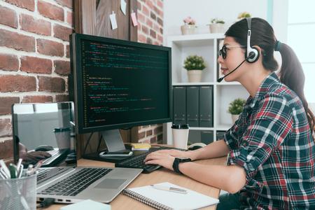 lächelnder freundlicher Frauenbetreiber, der Kundencomputer durch Fernsystem überwacht und Datencode des Computers zur Lösung des Problems benutzt. Standard-Bild