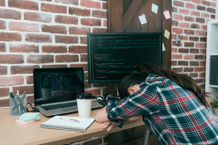professional young computer engineer woman design code data system  overwork in office feeling tired and sleeping on working desk resting. Stock Photo
