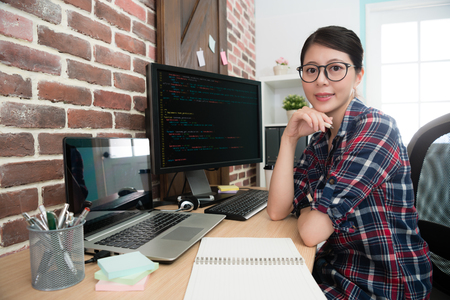 confident professional female programmer worker face to camera smiling when she sitting on workplace doing development new internet system.