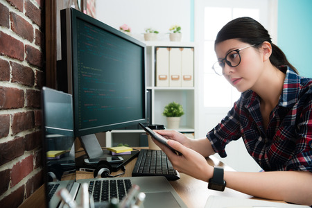 elegant attractive female programmer using mobile pad computer working and looking at laptop to think new website design idea.