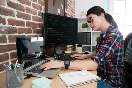 seriously pretty woman office worker programming internet system with code language in office.