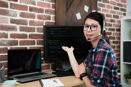 confident pretty programming company service center female operator looking at camera and making presentation posture showing code language.