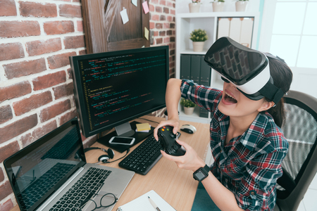 cheerful happy woman computer engineer finished work and using virtual reality device playing online game and enjoying 3D simulation video relaxing. Stok Fotoğraf