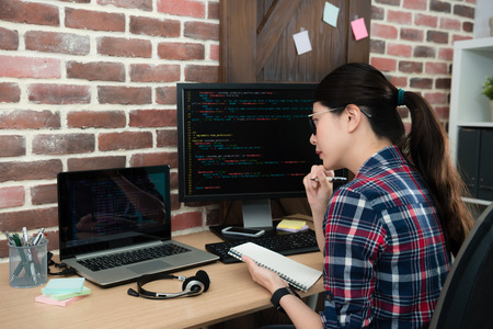 young beautiful female office worker working on programming company and holding personal notebook looking at mobile laptop thinking new design idea.