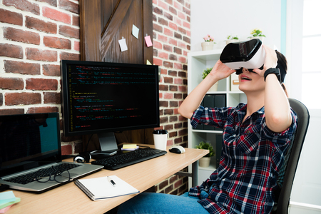 smiling pretty female business worker sitting on workplace and wearing VR technology device watching video enjoying 3D simulation game. Stock Photo
