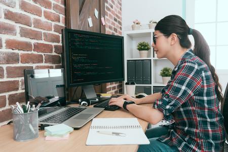 schoonheid glimlachende vrouwelijke programmeur met behulp van computer werkt op kantoor en het typen van gegevenscode voor het ontwikkelen van nieuwe systeembescherming online gebruikersbeveiliging.