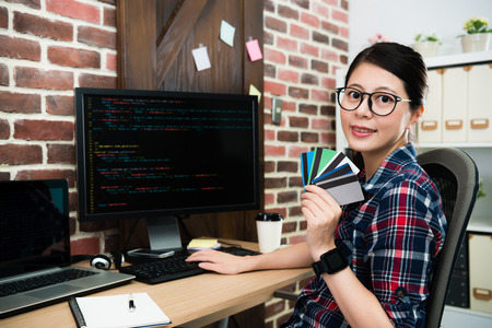 professional pretty programming company office worker woman showing many credit card looking at camera smiling when she development online protection system.